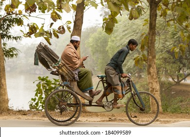 DHAKA, BANGLADESH - JANUARY 14, 2014: A man riding in a cycle rickshaw consults his cell phone.