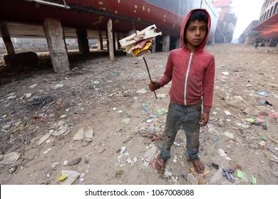 DHAKA - BANGLADESH - JANUARY 17, 2018: Unidentified street child collects trash on January 17, 2018 in Dhaka, Bangladesh. Bangladesh has an estimated number of above 670,000 street children