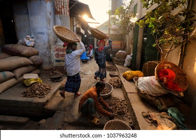 DHAKA - BANGLADESH - JANUARY 20, 2018: Unidentified porters carry baskets in the traditional market on the riverbank of the Buriganga River on January 20, 2018 in Dhaka, Bangladesh