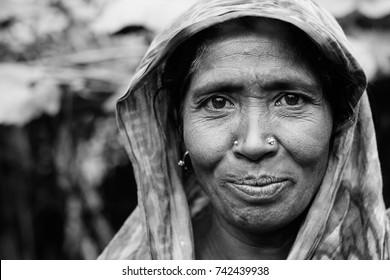 DHAKA, BANGLADESH JANUARY 21 2016: a portrait of an unidentified woman farmer posing at her house in an island at the brahmaputra river in rural bangladesh inhabited by climate refugees