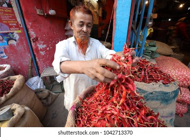 DHAKA - BANGLADESH - JANUARY 26, 2018: Unidentified market vendor sells chilies in the market on the riverbank of the Buriganga River on January 26, 2018 in Dhaka, Bangladesh