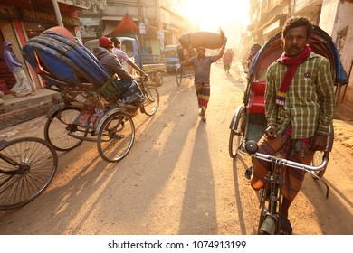 DHAKA - BANGLADESH - JANUARY 26, 2018: Unidentified rickshaw driver in the traditional market on the riverbank of the Buriganga River on January 26, 2018 in Dhaka, Bangladesh
