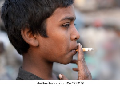 DHAKA - BANGLADESH - JANUARY 28, 2018: Unidentified street child smokes a cigarette on January 28, 2018 in Dhaka, Bangladesh. Bangladesh has an estimated number of above 670,000 street children