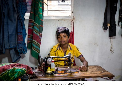 DHAKA, BANGLADESH - JANUARY 6, 2017: Young boy wearing a yellow shirt behind a sewing machine doing child labour