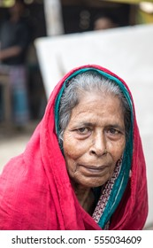 DHAKA, BANGLADESH - JANUARY 8, 2017: Old bangladeshi women is cold and covered in a red blanket