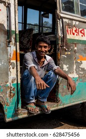 DHAKA, BANGLADESH - JANUARY 8, 2017: Young boy from rural Dhaka sitting on the stairs of an old bus in Dhaka