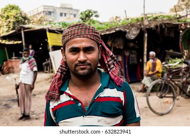 DHAKA, BANGLADESH - JANUARY 8, 2017: Portrait of a man in Bangladesh wearing a head scarf and a green, white and red striped shirt, with the slums of dhaka in the background