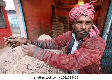 DHAKA - BANGLADESH - JANUARY 8, 2018: Unidentified market vendor smokes a cigarette in the market on the riverbank of the Buriganga River on January 8, 2018 in Dhaka, Bangladesh