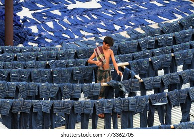 DHAKA, BANGLADESH - JULY 19, 2014: A worker collects pairs of dyed jeans from rooftops in the apparel hub of Keraniganj in Dhaka, Bangladesh on July 19, 2014.