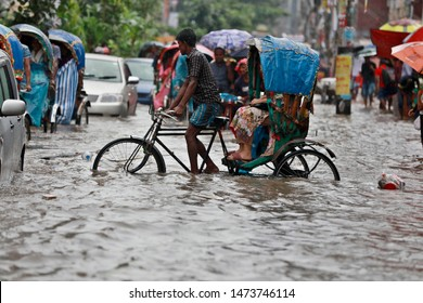 Dhaka, Bangladesh - July 24, 2018: Vehicles try to drive through a flooded street in Dhaka, Bangladesh. Encroachment of canals is contributing to the continual water logging in the Capital Dhaka.