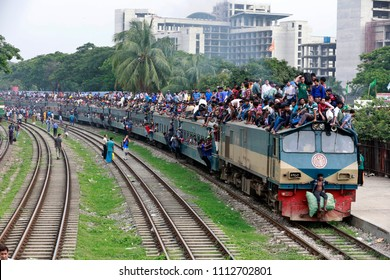 Dhaka, Bangladesh - June 14, 2018: Bangladeshi people on top of trains as they travel to their hometowns ahead of the Muslim holiday of Eid al-Fitr, in Dhaka, Bangladesh on June 14, 2018.