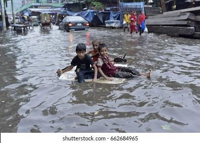 DHAKA, BANGLADESH - JUNE 19, 2017: Bangladeshi children row a makeshift raft on a flooded road in Dhaka, Bangladesh on June 19, 2017.