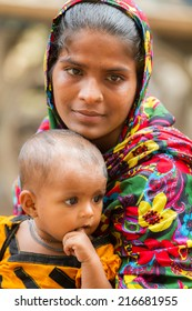 DHAKA, BANGLADESH - JUNE 6, 2014: A young Bangladeshi mother with her baby in Old Dhaka.
