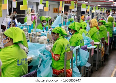 Dhaka, Bangladesh - March 31, 2020: Workers producing personal protective equipment (PPE) for health professionals at a garment factory of Urmi Group in Dhaka on March 31, 2020.