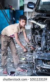 DHAKA, BANGLADESH - MARCH 5, 2018: A young boy doing child labor work in a car mechanic workshop