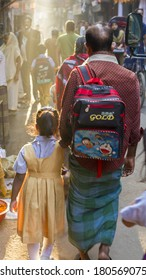 DHAKA, BANGLADESH - MARCH 8, 2014: A man walks his daughter to school on a busy street in Old Dhaka.  Girls education has increased sharply in Bangladesh in recent years.