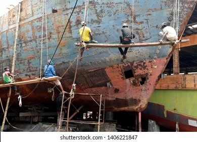 Dhaka, Bangladesh - May 23, 2019: Bangladeshi laborers works on a ferry being refurbished at a dockyard at Keraniganj in Dhaka, Bangladesh on May 23, 2019.