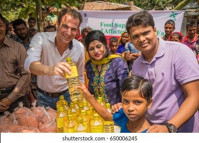 DHAKA, BANGLADESH - MAY 26, 2017: Two local bangladeshis and one western foreigner are donating emergency food supplies to poor people in a charity donation after the flooding