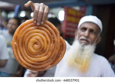 DHAKA, BANGLADESH - MAY 28, 2017: On the first day of Muslim fasting month of Ramadan, a Bangladeshi vendor sells traditional Iftar at Chawk Bazar in Dhaka, Bangladesh on May 28, 2017.