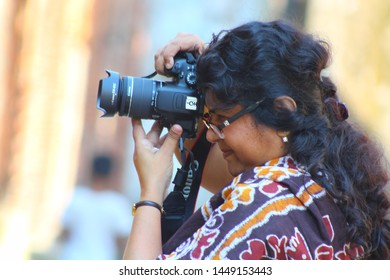 Dhaka / Bangladesh - November 18, 2016: Woman Photographer in action, Professional female photographer concentrate and continue his passion for photography. World photography Day.