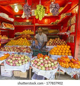 DHAKA, BANGLADESH - NOVEMBER 23, 2013: A shopkeeper in Old Dhaka sits in his fruit stall waiting for clients.  Small shops are the most common retail sales points in Bangladesh.