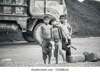 DHAKA, BANGLADESH - SEPTEMBER 24, 2017: Black and white picture of three poor children who are posing in front of a truck in a third world development country