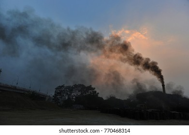 DHAKA, BANGLADESH-OCTOBER 22, 2016: Dark Black smoke rises from a road construction site in Dhaka, Bangladesh. In rapidly-industrializing countries such as India, Pakistan and  Bangladesh,