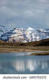 Dhankar lake and snowcapped Himalayas mountains. Spiti Valley, Himachal Pradesh, India