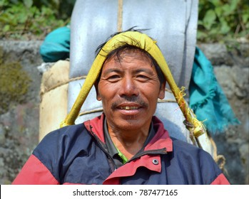 DHARAPANI, ANNAPURNA CIRCUIT, NEPAL - APR 13, 2016: Nepali mountain porter with heavy load and tumpline takes a short break on a stone bench on the Annapurna Trek, on April, 13, 2016.