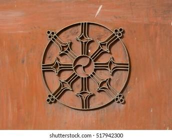 Dharma Wheel Buddhist symbol in old door of local temple in Ladakh, India.