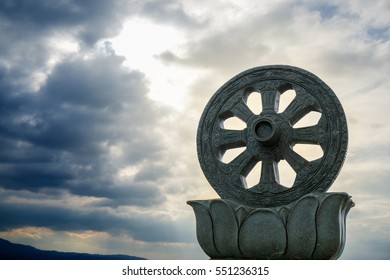 Dharmachakra or Wheel of Dhamma Symbol of Buddhism, Carved sandstone on the blue sky background