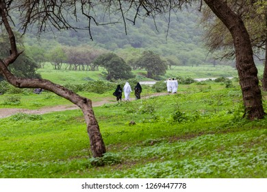 DHOFAR, OMAN - AUGUST 20, 2015: Men and women wearing national dress walking in Wadi Darbat, near Salalah, Dhofar Province, Oman, during the annual Khareef or monsoon