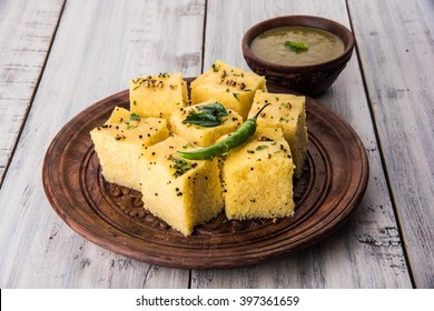 Dhokla is a veg food / snack / breakfast item from Indian state of Gujarat. Made with a fermented batter of from rice & split chickpeas/besan. served with chutney & chilli on wood or colourful base