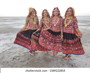 Dhordo, Gujarat / India - December 15 2019: Dancers standing at the Great Rann of Kutch in their colorful costumes during the Rann Utsav Festival