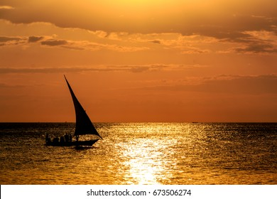 A dhow boat sails by as the sun sets over the Indian Ocean on the beach off the coast of the island of Zanzibar, with gorgeous yellow and orange golden light