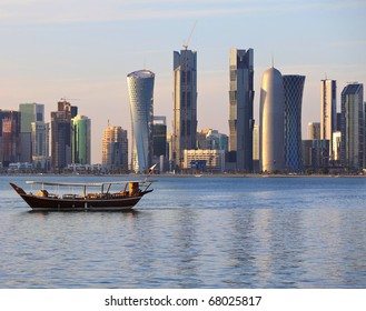 A dhow returns to harbour in Doha, Qatar, at sunset, with the city's modern skyline in the background.
