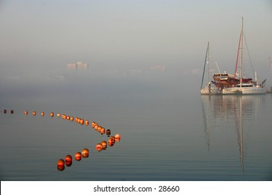 A dhow and a yacht at a marina in morning mist, Doha, Qatar