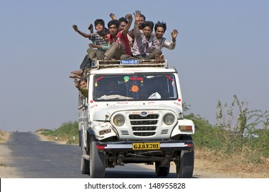 DHRANGADHRA, INDIA - MARCH 14: Unidentified travellers, mostly salt workers in the Little Rann of Kutch on March 14, 2012 near Dhrangadhra, Gujarat, India. Transport for workers is often overcrowded.