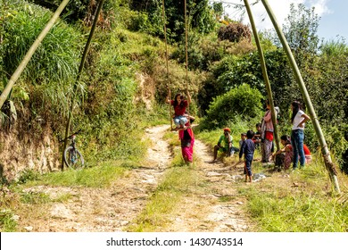 Dhulikhel, Nepal - Oct 18, 2018: A Nepalese girl plays swing made of bamboos during Dashain festival. Villagers in Nepal built the bamboo swings for kids to play during festival.