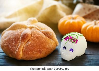 El Día de los Muertos: Cránula de azúcar (Calaverita) y pan de la oferta muerta, sobre mesa de madera, enfoque selectivo
