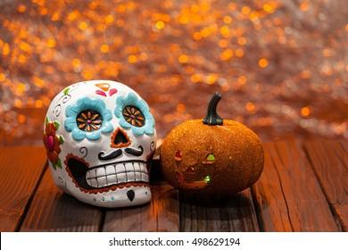 Dia De Los Muertos Halloween Celebration Background With Sugar Skull And Orange Pumpkin. Selective Focus With Copy Space.