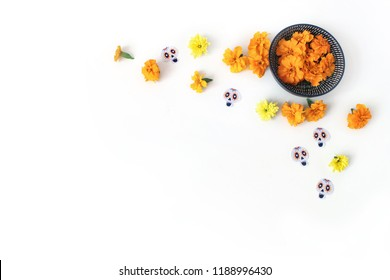 Dia de los Muertos, Mexican Day of the Dead desk composition. Orange tagetes, marigold, chrysanthemum flowers and decorative paper skull stickers. White table background. Halloween flat lay, top view