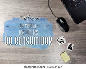 Dia mundial dos direitos do Consumidor. World consumer rights day. Text in Portuguese. notebook, mouse and shopping cart on wooden table. Shopping concept.