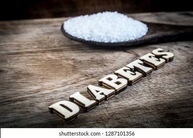 Diabetes block letters.Old wooden board background.Sugar pile.Old coconut timber spoon.