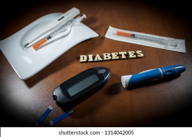 Diabetes block letters,insulin syringes,test strip,glucose meter and lancing device on table background.