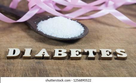Diabetes block letters.Wooden board background.Sugar pile.Wooden spoon.