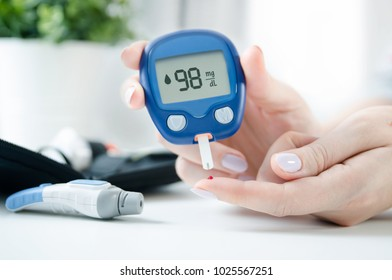 Diabetes checking blood sugar level. Woman using lancelet and glucometer at home.