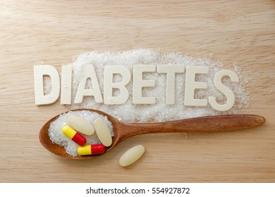 Diabetes concept. Alphabet with word DIABETES with sugar,tablet,pills,capsule and wooden spoon on wooden background.