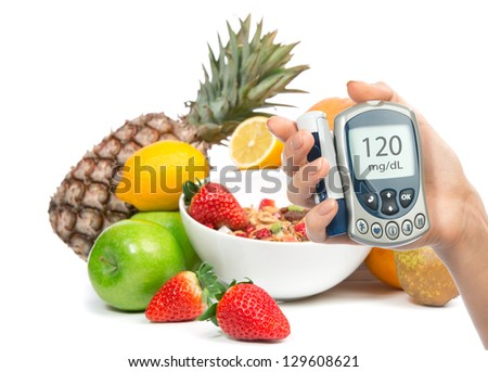 Diabetes concept glucose meter in hand and healthy organic food, lemon, pear, apples, fresh orange, pineapple and breakfast cereal muesli bowl on a white background