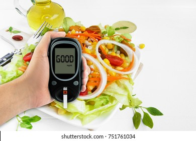 Diabetes diabetic concept Good of glucose meter in hand and healthy salad organic food  on a white background.